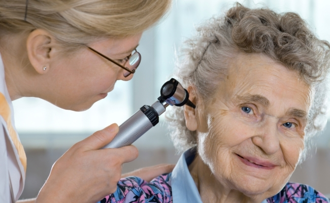 Elderly woman getting her hearing checked by an audiologist